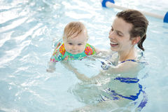 Baby and mom in the pool. A little baby girl having fun in an indoor public pool with her mother Royalty Free Stock Images