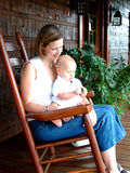 Baby and Mom on Porch. Baby boy and Mom on rocking chair on front porch of family home Royalty Free Stock Photo