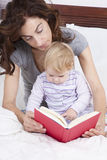 Baby and mom reading in bed Royalty Free Stock Photo