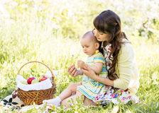 Baby and mom sit with basket outdoors Stock Photography