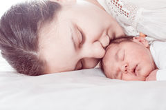 Baby with mom. Sleep baby with mom, closeup faces, mommy`s kiss royalty free stock photo