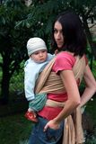 Baby with mom in sling stock photos