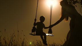 Baby and mom swinging on a swing in park in sun. silhouette of small healthy child on swing. daughter and mother love