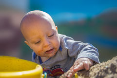 Baby 10-12 Monate alte, die im Sandkasten spielen Stockfotografie