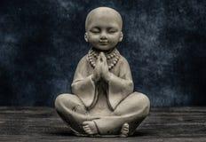 Baby monk praying statuette stock photos