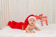 Baby 6 months in a Santa costume lying in a crib at home on his stomach, a gift for the new year. Christmas holiday concept