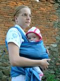 Baby with mother. Portrait of mother with her baby carrying her in sling Royalty Free Stock Photography