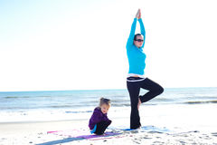 Baby and mother. Doing yoga at the beach Stock Image