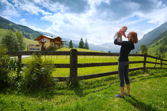 Baby and mother with the Alps mountains in nature in the Backgro Royalty Free Stock Images