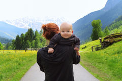 Baby and mother with the Alps mountains in nature in the Backgro Royalty Free Stock Photography