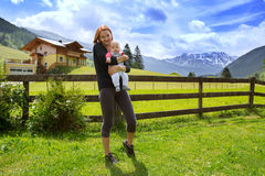 Baby and mother with the Alps mountains in nature in the Backgro Royalty Free Stock Photos