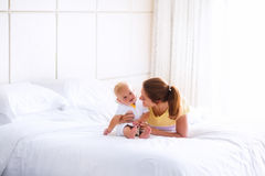 Baby and mother in bed Stock Photos