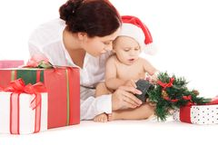Baby and mother with christmas gifts. Over white (focus on baby royalty free stock photography