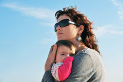 Baby Mother Daughter. Mother hugs her baby daughter with blue sky in background Stock Photo