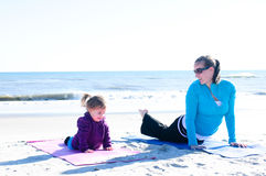 Baby and mother doing yoga. Mother and child doing yoga on the beach Royalty Free Stock Photos
