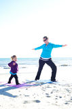 Baby and mother doing yoga. At the beach Royalty Free Stock Photography