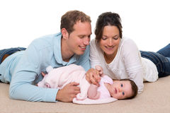 Baby mother and father happy family lying on carpet. Baby mother and father happy family portrait  lying on carpet and white background Stock Photos