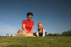 Baby, mother, grass and sky. Baby and his mother are having outdoor fun together and they are smiling a lot. There are nice afternoon lights Royalty Free Stock Photography