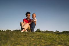 Baby, mother, grass and sky. Baby and his mother are having outdoor fun together and they are smiling a lot. There are nice afternoon lights Stock Image