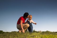 Baby, mother, grass and sky. Baby and his mother are having outdoor fun together and they are smiling a lot. The mother is kissing his son. There are nice Stock Images