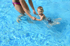 Baby with mother. Mother with happy baby in the swimming pool Stock Images