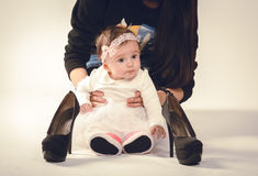 Baby with mother and looking at high heel shoes Stock Photography
