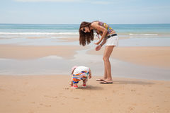 Baby and mother looking for sea shells Stock Image