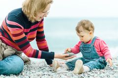 Baby and mother play with pebbles on the beach. Baby and mother play with pebbles. Happy family is on the sea beach in spring. One-year-old child in denim looks stock photos