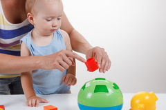 Baby and Mother play with toy in blue dress smiling Royalty Free Stock Photo