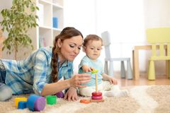Baby and mother playing toy rings. Toddler kid plays pyramid, children early education royalty free stock images