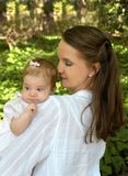 Baby on Mother's Shoulder. Mother looks down lovingly at her tiny infant daughter.  Both have on white and have brown hair.  They are outside in a garden with Royalty Free Stock Photos