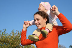 Baby on mother shoulders stock images