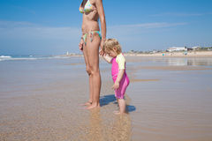 Baby and mother standing at shore Royalty Free Stock Photos