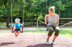 Baby mother swing playground looking each other Royalty Free Stock Image