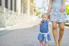 Baby with mother walking in city Stock Photos