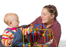 Baby with motor activity development delay. Being stimulated to develop coordination and muscle control and movement on a bead maze by an adoring mother Stock Photo