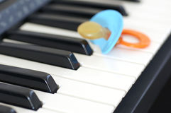 Baby and music. Concept. Music helps babies relax. One is never too young to start learning how to play music. Closeup shot of pacifier and piano Stock Images