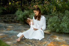 Baby in my arms. Woman sits on garden path and holds her tiny infant.  They are both dressed in white.  Mom has long hair and child has hair with tiny bow.  Mom Royalty Free Stock Photo