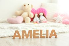 Baby name AMELIA composed of wooden letters on floor. Choosing name concept royalty free stock photography