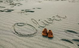 Baby name written in sand with shoes. Baby name Oliver written in the sand next to his shoes royalty free stock photos