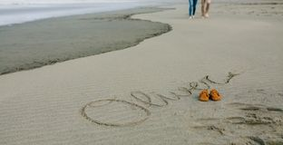 Baby name written in sand with shoes. Baby name Oliver written in the sand next to his shoes while the parents take a walk royalty free stock image