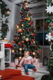 Baby near the Christmas tree. Baby girl is sitting near the Christmas tree with presents Stock Images
