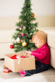 Baby near Christmas tree Stock Photos