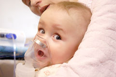 Baby with nebulizer mask stock photo