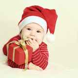 Baby and New Year or Christmas gift. Baby in Santa hat and New Year or Christmas gift royalty free stock images