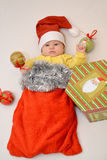 The baby in a New Year`s suit of Santa Claus with Christmas tree decorations.  royalty free stock photo