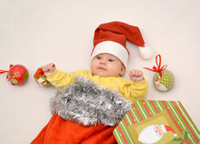 The baby in a New Year's suit of Santa Claus with Christmas tree decorations. On a light background royalty free stock photos