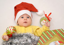 The baby in a New Year's suit of Santa Claus with Christmas tree decorations Royalty Free Stock Photography