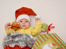The baby in a New Year's suit of Santa Claus with Christmas tree. Decorations on a light background royalty free stock photography