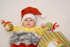 The baby in a New Year's suit of Santa Claus with Christmas tree. Decorations on a light background stock photo
